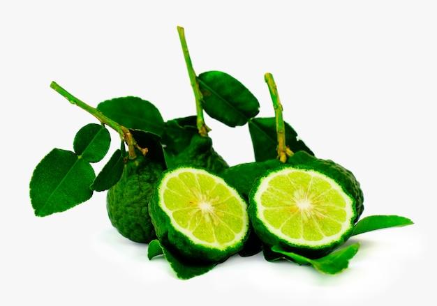 Close up a cut half of bergamot fruit and leaf on white background