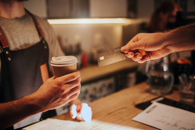Close up and cut view of a barman hand holding a cup of coffee and giving it to the customer. at the same time the customer is giving him a credit card to pay for order.