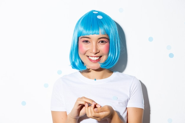 Close-up of cute asian girl in blue wig celebrating halloween, throwing confetti and smiling, standing.