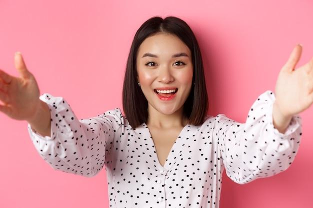Primo piano di una donna asiatica carina che allunga le mani in avanti, scatta selfie, registra un blog di bellezza e sorride, in piedi su sfondo rosa.