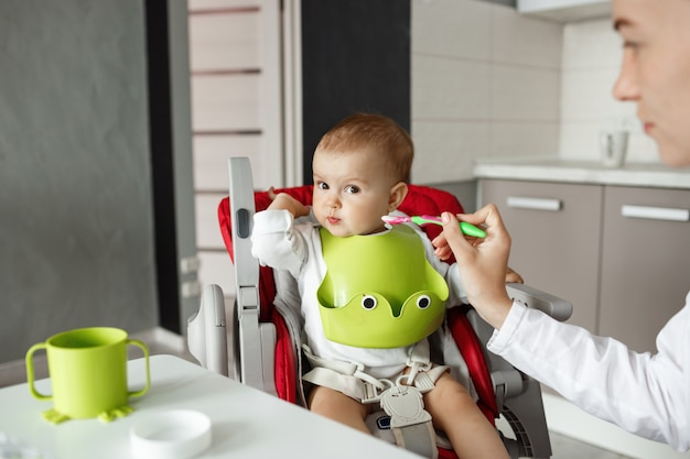 Close up of cute baby son sitting in kitchen in baby chair and turning head aside refusing to eat baby food. mother tries to feed him with spoon.