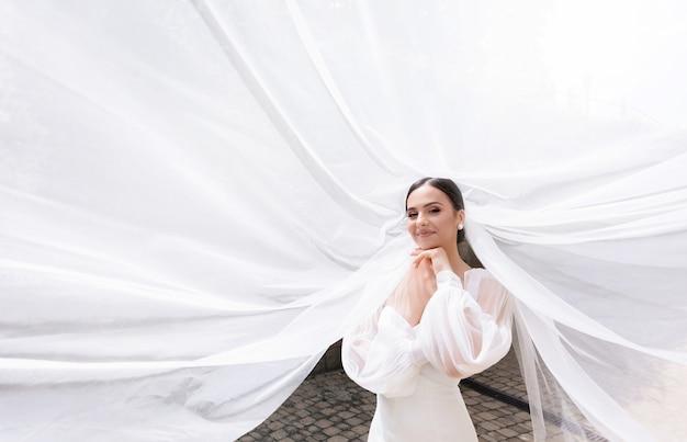 Primo piano di una bella sposa bruna in piedi e sorride alla telecamera