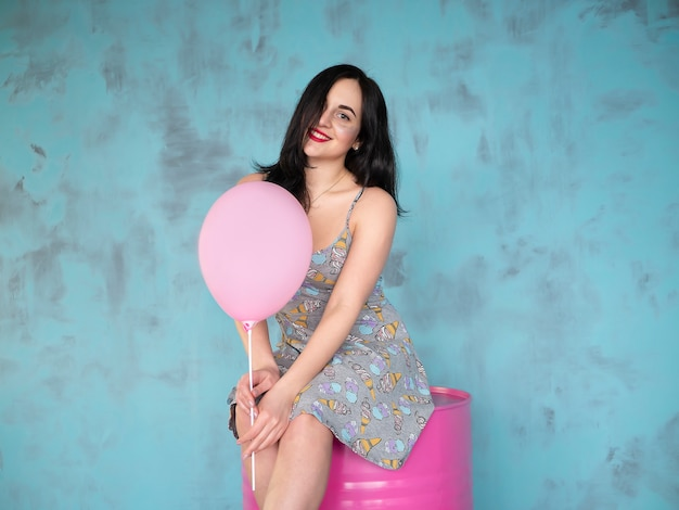 Close-up of cute brunette girl standing in a studio, smiling widely and playing with pink baloon.