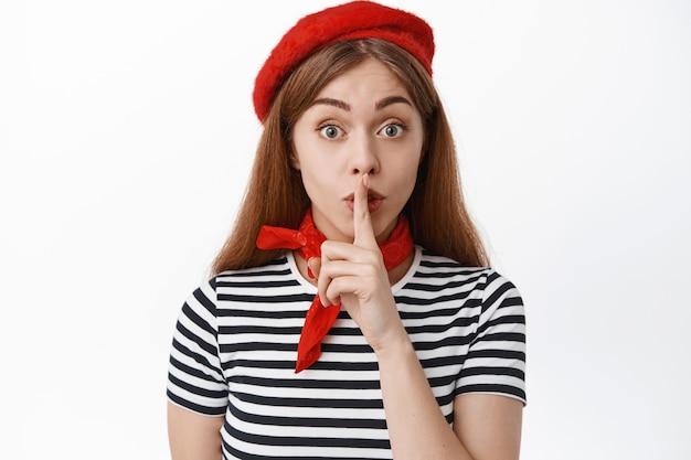 Primo piano di un simpatico modello femminile in berretto rosso francese che nasconde un segreto, facendo segno shh shush, premi il dito sulle labbra, chiedi di tacere, rimani in silenzio, in piedi sul muro bianco