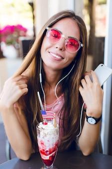 Primo piano della ragazza carina seduta in un caffè a mangiare il gelato con la ciliegina sulla torta. indossa un top rosa e occhiali rosa. ascolta la musica sullo smartphone e sorride. ha lunghi capelli scuri