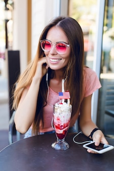 Close-up of cute girl sitting in a cafe eating ice-cream with cherry on top. she wears pink top and pink eyeglasses. she listens to music on smartphone and smiles. she has long dark hair