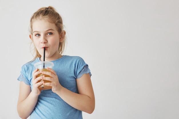 Primo piano di ragazza carina con i capelli chiari in acconciatura coda tenendo il bicchiere di latte in mano, bevendo attraverso la paglia e guardando da parte con la faccia buffa.