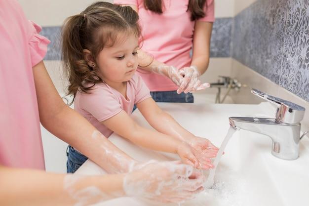 Close-up cute girls washing hands