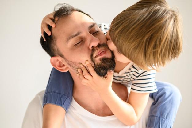 Крупным планом милый ребенок целует сына