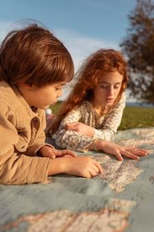 Close-up cute kids looking at map