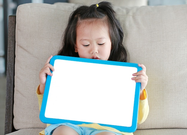 Close up cute little child girl holding empty white blackboard on fabric sofa