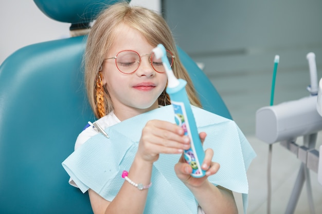 Close up of a cute little girl holding electric toothbrush, sitting in dental chair