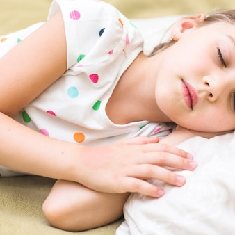 Close-up of cute little girl sleeping on bed