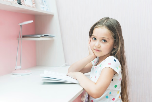 Close-up of cute little girl studying