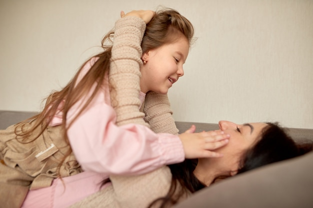 Close up of cute little preschool girl play with young mother, small daughter hug embrace happy mom