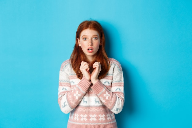 Primo piano della ragazza carina rossa che guarda con anticipazione e preoccupazione, fissando la telecamera, in piedi in un maglione invernale su sfondo blu.