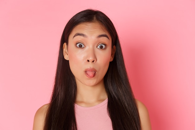 Close-up of cute and silly, kawaii asian girl making funny faces, showing tongue as mocking someone,