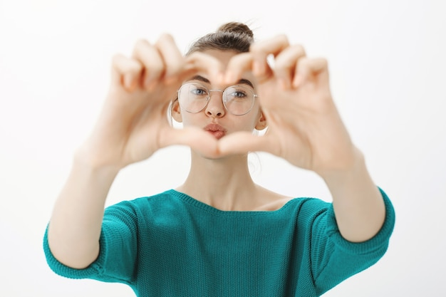 Close-up of cute and silly young woman in glasses showing heart gesture and looking through it with pouting face