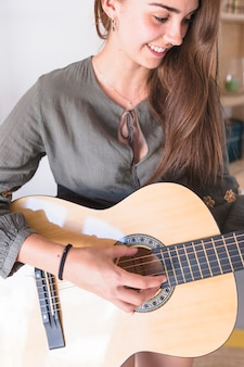 Close-up of a cute teenage girl playing guitar