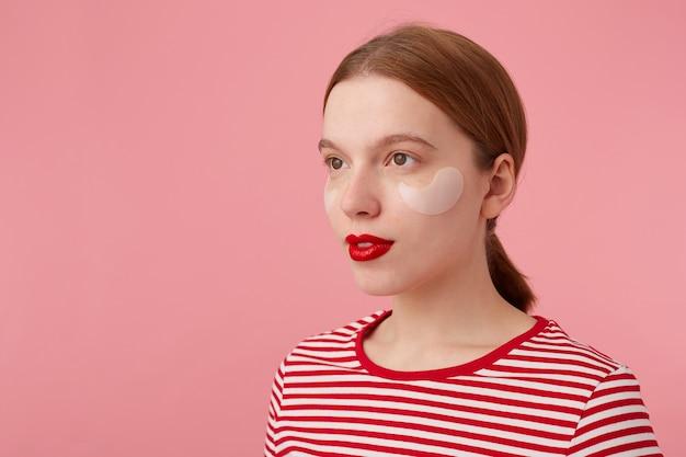 Primo piano di carino giovane signora allo zenzero con labbra rad, indossa una maglietta a strisce rossa, guarda con un'espressione calma, si alza.