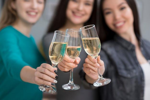 Крупным планом милые молодые женщины, имеющие шампанское вместе