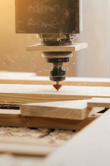 Close-up of cutting wood on a cnc milling machine in garage