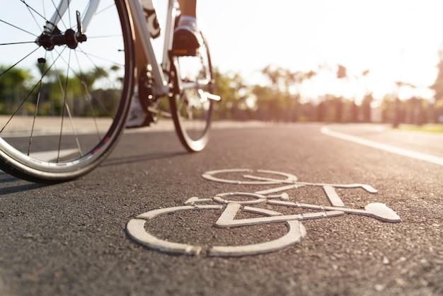 アスレチック女性サイクリストの足で道路にサイクリングのロゴ画像を閉じる
