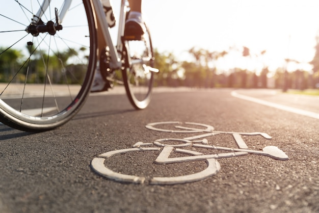 Close up cycling logo image on road with athletic women cyclist legs