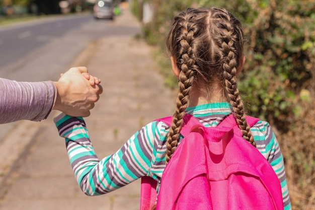 Close-up a dad is seeing off or leading his daughter with a backpack or knapsack to school