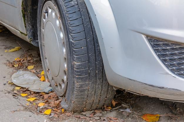 클로즈업 손상 된 타이어입니다. 자동차 타이어의 바퀴 누출. 수리를 기다리는 펑크난 타이어. 주차장에 버려진 차.