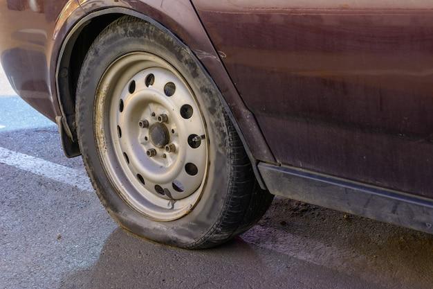 클로즈업 손상 된 타이어입니다. 자동차 타이어의 바퀴 누출. 수리를 기다리는 펑크난 타이어. 주차장에 버려진 차. 프리미엄 사진