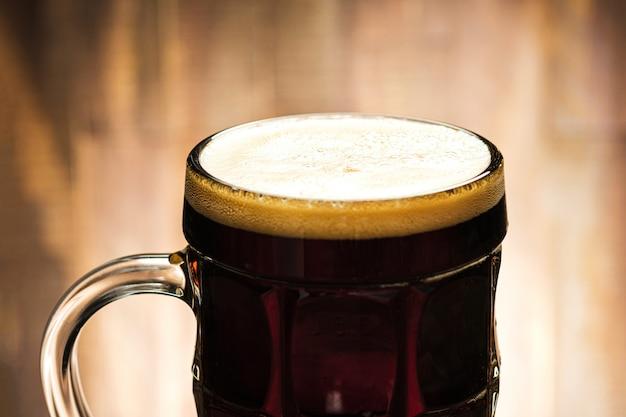 ガラスの泡とクローズアップのダークビール