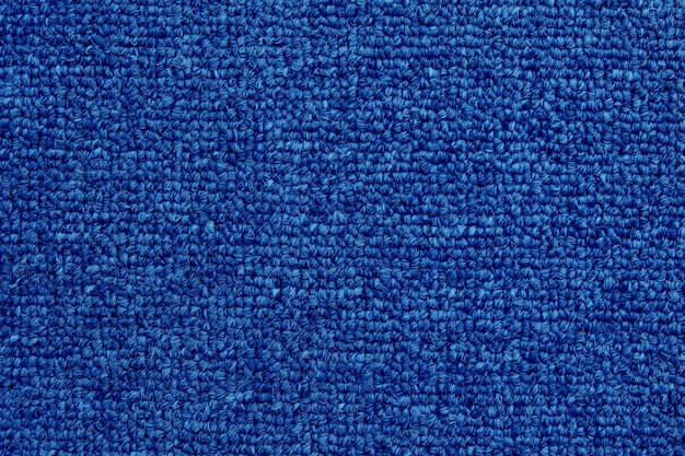 Close up of dark blue color carpet texture background with seamless pattern.