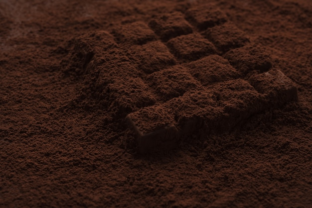Close-up of a dark chocolate bar covered in chocolate powder