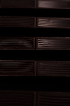 Close-up of dark chocolate bar tiles in a line