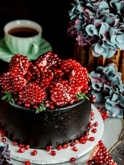 Close up of dark chocolate cake topped with pomegranate seeds