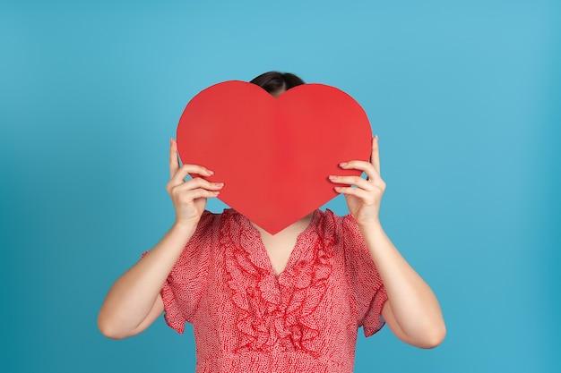 Крупный план темноволосая женщина в красном платье прячет лицо за большим красным бумажным сердцем