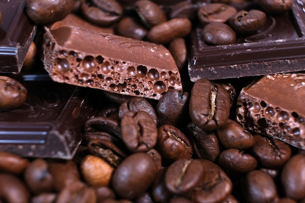 Close-up of dark roasted coffee beans and chocolate background.