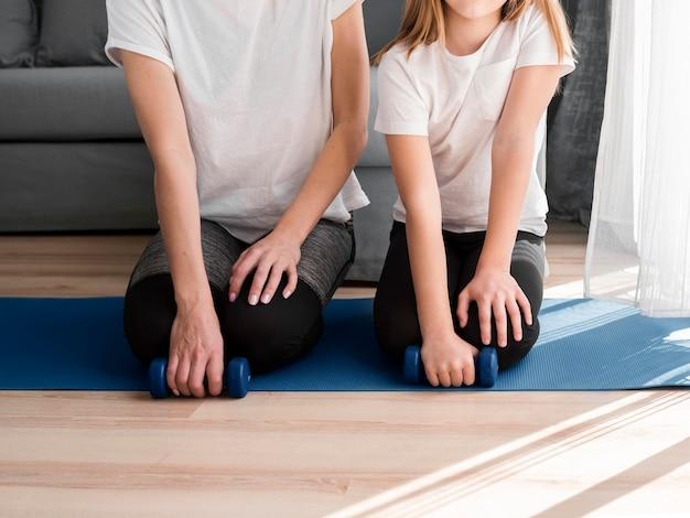 Дочь и мама крупным планом занимаются спортом