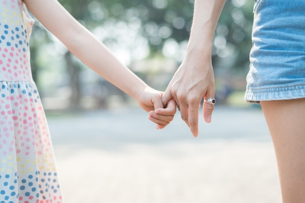 Close up daughter hand holding with her mother , feel comforted  and affectionate, happy family time