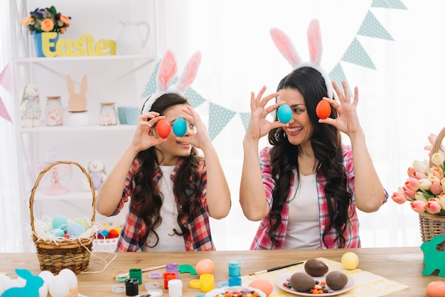 Close-up of a daughter and her mother holding red and blue easter eggs in hand looking at each other