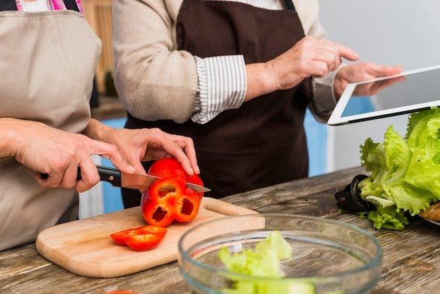 Close-up of daughter standing with her mother holding digital tablet cutting bell pepper with knife