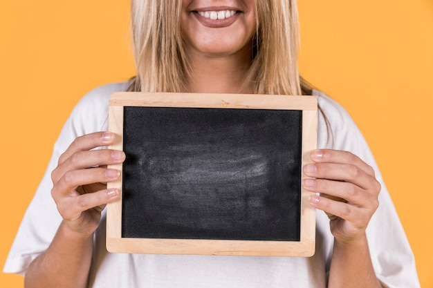 Close-up of a deaf woman standing with blank slate over yellow background