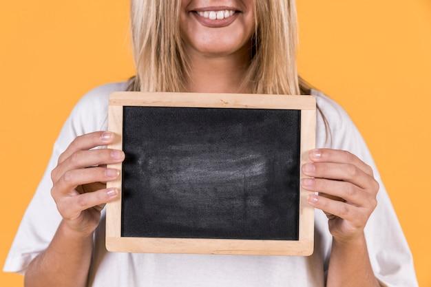Primo piano di una donna sorda che sta con l'ardesia in bianco sopra fondo giallo