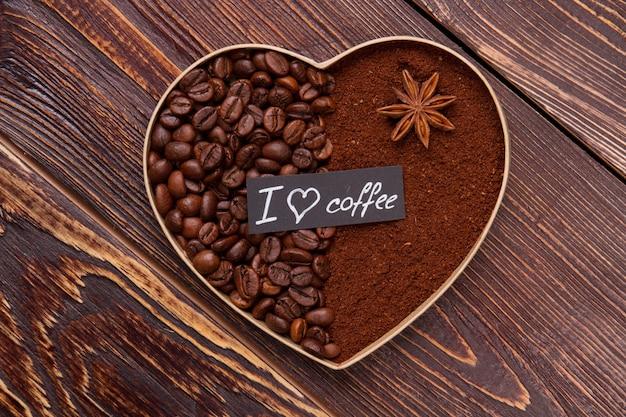 Закройте вверх по декоративному сердцу кофе на деревянном столе. кофейные зерна с растворимым кофе и анисом.