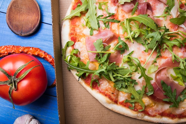 Close-up of delicious bacon and arugula pizza in box with garlic; tomato and chili on table