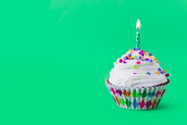 Close-up of delicious cupcake with burning candle on green background