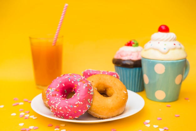 Close-up of delicious donuts and muffins on yellow background