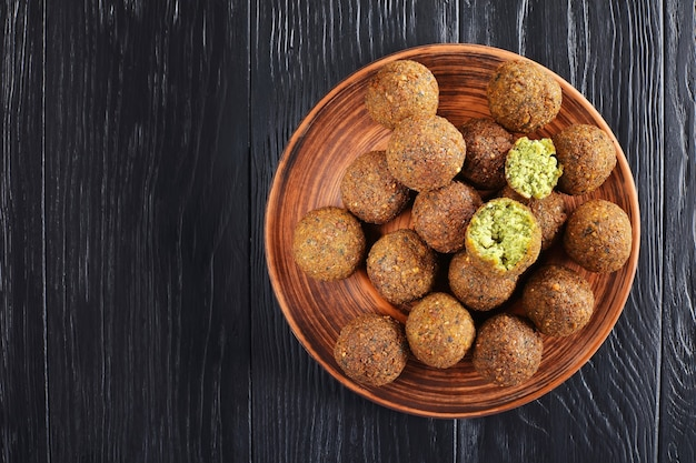 Close-up of delicious falafel balls on clay plate on black wooden table