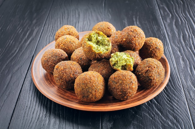 Close-up of delicious falafel balls and one is broken to pieces on a clay plate on black wooden table
